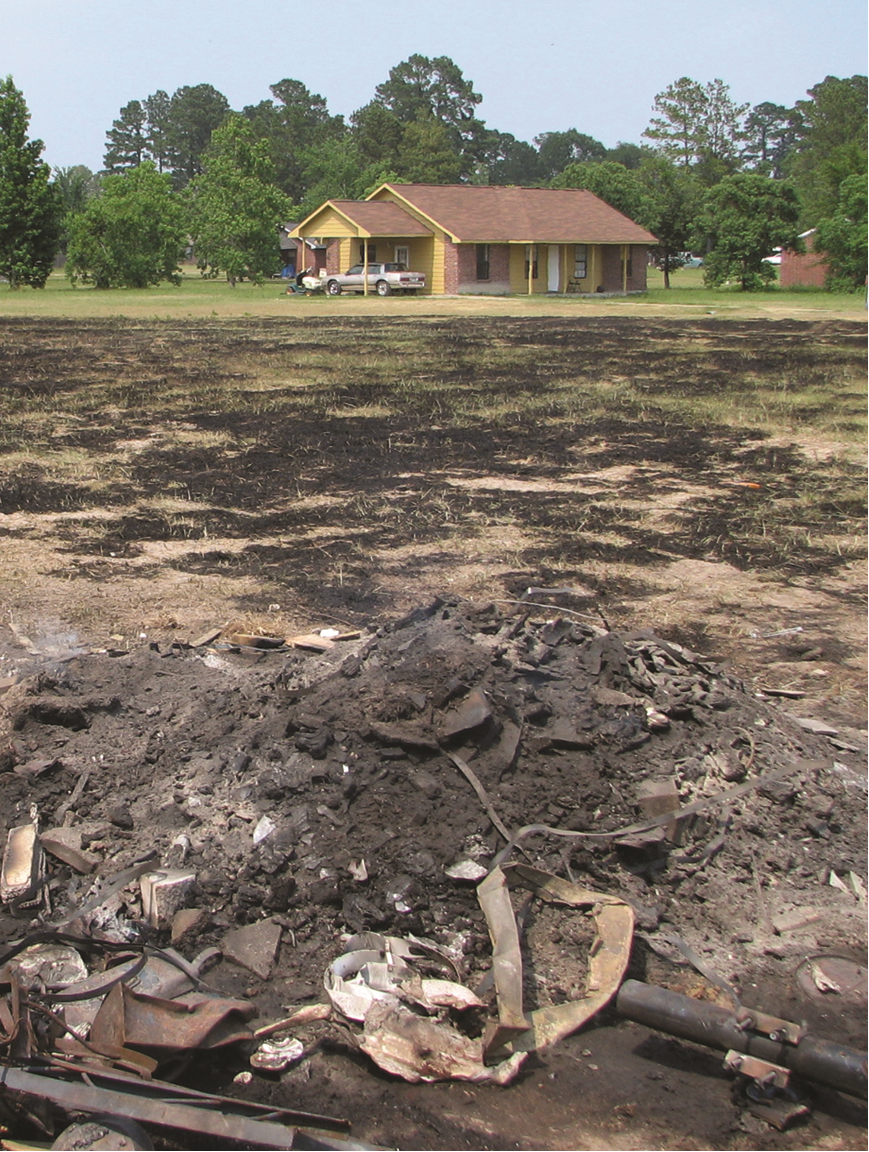 Burned field and debris in front of house.