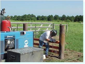 Man welding a gate with a welding mask on standing beside his equipment