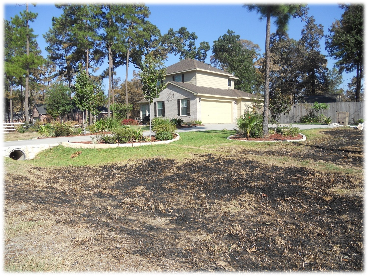 BURNT GRASS LEADING UP TO NON-COMBUSTIBLE LANDSCAPING