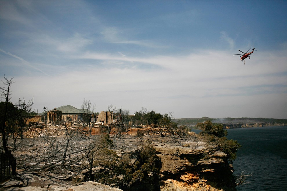 TWO HOUSES SURROUNDED BY ASHES FROM A WILDFIRE. ONE HOME IS BURNT DOWN, WHILE THE OTHER REMAINS STANDING