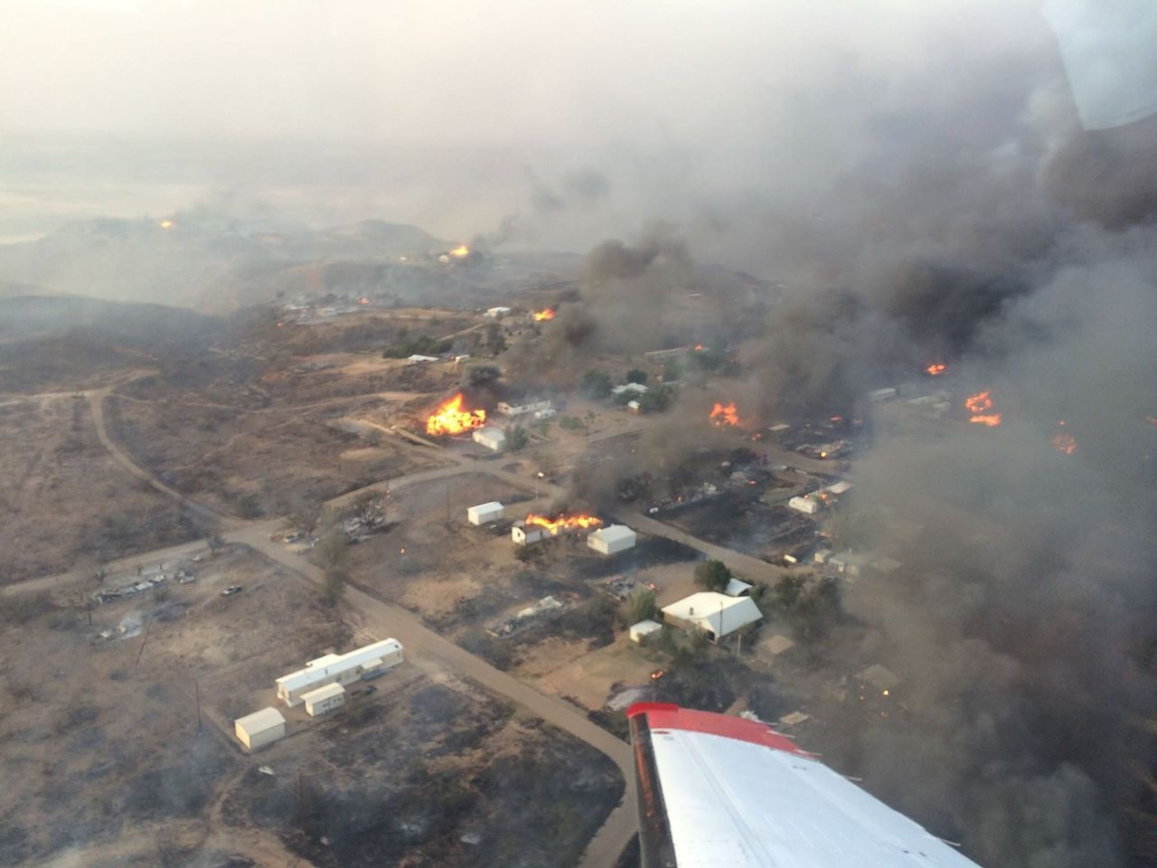 Aerial view of a wildfire in a community with smoke throughout the sky