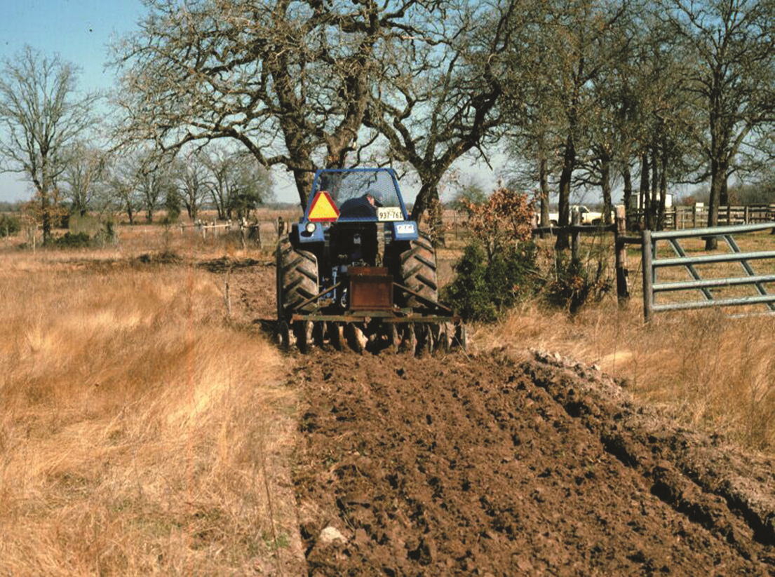 Tractor plowing a field while installing a fire break