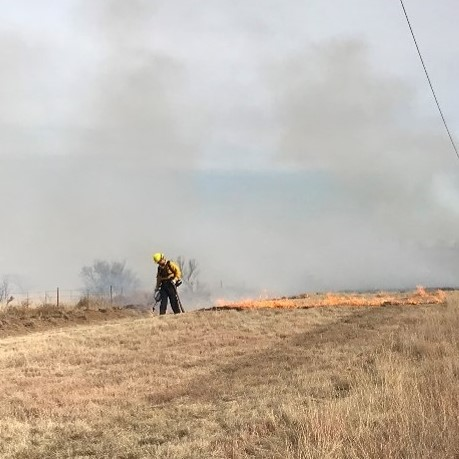 Man in protective fireline gear conducting a prescribed burn in an open field